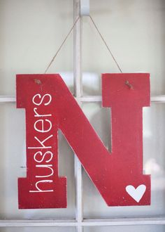 Hello fellow husker fans! This door hanger measuring approximately 16x16. This piece comes in three colors: black with white lettering, red with white lettering, and white with black lettering. This piece will come lightly distressed and sealed and ready to hang with ribbon and was made with extra husker pride! Please message me for any customized options you may want! Thank you for stopping by and GO BIG RED