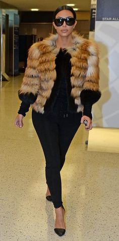 To catch a flight at JFK International Airport, Kardashian wore a fluffy multicolored fur coat, leggings, and a sheer top and accessorized with a pair of black stilettos and sunglasses.