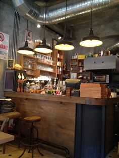 Exposed ducts in ceiling give industrial feeling - Ops Cafe Lampes et bar
