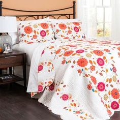 "Refresh your guest room or master suite with this charming cotton quilt set, showcasing a scalloped border and floral motif.   Product: Full/Queen: 1 Quilt and 2 standard shamsKing: 1 Quilt and 2 king shamsConstruction Material: Cotton and polyesterColor: Fucshia and orangeFeatures:  Scalloped borderReversible quiltDimensions: Standard Sham: 20"" x 26""Full/Queen Quilt: 92"" x 88""King Sham: 20"" x 36""King Quilt: 92"" x 108""Note: Shams do not include insertsCleaning and Care: Machine washable"