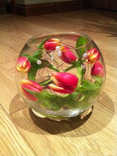 A simple fish bowl arrangement. Fill your bowl with around an inch of clean water. Leave your tulips out of water for a few hours, until they are 'floppy' Cut the stems, arrange gently inside the bowl, ensuring the base of the stems are under water and your done. Easy! Happy arranging Pinners