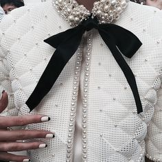 White jacket with trim/pearl brooch