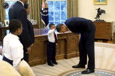 President Barack Obama bends over so that the son of a White House staff member can pat his head during a family visit to the Oval Office in this handout photo taken in Washington.