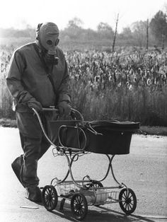 A Chernobyl liquidator pushes a baby in a carriage who was found during the cleanup of the Chernobyl nuclear accident, 1986
