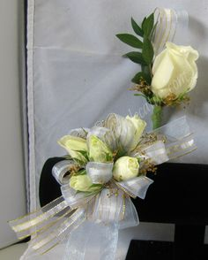 Light Blue and gold ribbon surround these pretty white spray roses. Shown here on our elastic band with matching boutonniere. $39.99 for the set. The Secret Garden in Decatur Illinois wants to be your prom corsage & boutonniere headquarters. Come and visit our corsage bar to create your own one of a kind corsage!