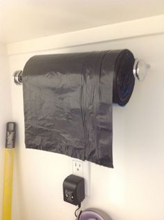 Paper towel holder for garbage bags. Great idea for a garage or work area