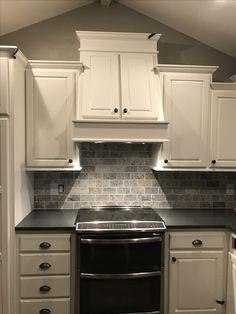 Cabinets-- Sherwin Williams Greek Villa  GE Profile double oven Vent hood with storage Maui quartz countertop Silver travertine backsplash  Walls-- Sherwin Williams Requisite Gray
