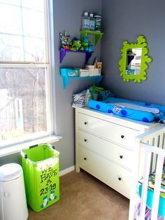 "My Monsters Inc Nursery - Changing table area with DIY ""We have a 23-19"" laundry bin and dresser and mirror from Ikea. Spray painted white shelves from Target."