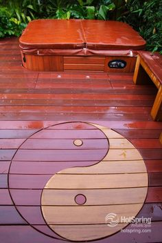 Custom yin  yang deck work with an integrated hot tub — fun backyard project for some unique yard décor.