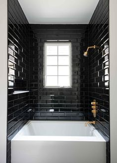 Black subway tile creates bold contrast against the bright white bathtub in this contemporary bathroom. A gold showerhead and faucet brings metallic glam to the space.