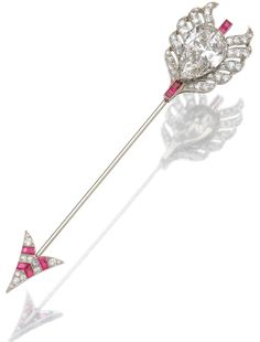 RUBY AND DIAMOND JABOT PIN, CIRCA 1920  Designed as an arrow, the feathers set to the centre with a pear-shaped diamond weighing 12.36 carats, the feathers and arrow head set with single- and circular-cut diamonds, highlighted with calibré cut rubies, French assay and indistinct maker's marks, fitted case signed Louis Aucoc Fils & Georges Aucoc, 9 Rue du 4 Septembre, Paris.
