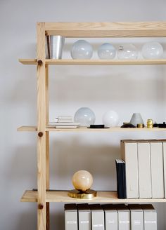 Wooden shelves hold an elegant miscellany of office materials, as well as a gleaming line-up of hand-blown glass—remnants of an experiment past.