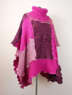 A colourful , patchwork poncho to keep you warm in the colder weather. Made from several recycled wool, alpaca, wool mix and cotton jumpers in shades of pink with a bit of black and white. It has a cosy, roll neck and wavey seams with exposed , dusky pink stitching. Lots of different textures.  * Size free. * Total length, end to end, 60 inches, 153 cm. * Width 42 inches, 107 cm.
