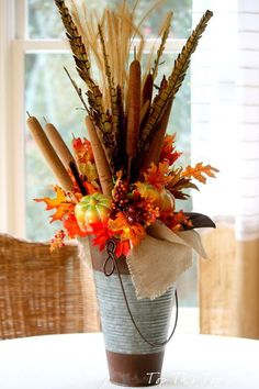 "Pheasant Feather Floral Arrangement — by Laura from Duke Manor Farm. She says that fall decorations are fast and easy since all the natural elements like the pheasant feathers and cattails ""naturally"" look good together."