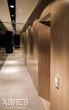 Widok od strony salonu. Długi hol zakończony jest zabudową narożną , część wieńcząca korytarz składa się z dwudrzwiowej szafy z frontami lustrzanymi, część po prawej stronie składa się z szafy narożnej wykończonej drzwiami fornirowanymi, które przechodzą w okładzinę ściany na całej długości przedpokoju.