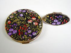 "This goldtone Stratton set contains a compact and a lipstick holder.  The compact features a black lid with a colorful floral motif.  This style compact has an inner ring with secure clasp.  The outer clasp is secure.   This compact measures  3"" in diameter.  The lipstick holder has a secure clasp and clear mirror.  It measures  2"" in length and  1"" in width.  This set is in pristine condition"