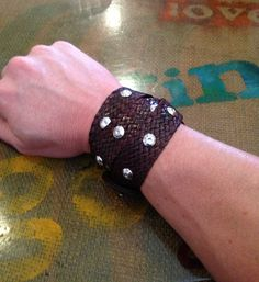 Studded wrist wrap.   Old braided red leather belt - $2.00. Brown leather dye - $12.90. Push in silver studs - $7.99.
