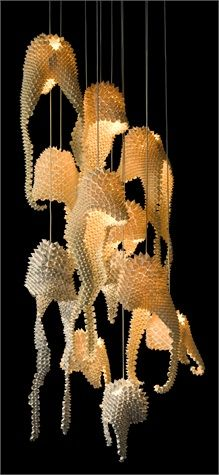 Suspension lamp with chromed metal frame and shade constructed of origami paper in the shape and texture of a dragon's tail.