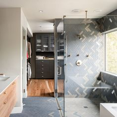 The bathroom receives plenty of natural light through the large window. This allowed for deeply toned tiles on walls and floor. To add interest the subway tiles were placed in a herringbone pattern.