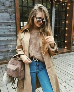 Beige fall: beige coat and knitted beige sweater tucked into jeans and a suede mini backpack. Casual street style for fall.