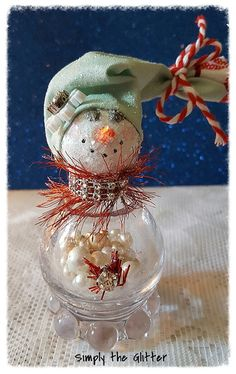 I really love the shape of this shaker...round, just like a snowman should be!!! Eleanor was made using a vintage glass salt shaker filled with vintage faux pearl beads and mica flakes. Her hat is a handmade stocking cap made from light green Christmas fabric tied with red and white bakers twine. There is a white snowflake with a rhinestone bead on the brim of the hat. Her scarf is red eyelash trim with rhinestone trim. Her button is red garland with a rhinestone in the middle.  Her head is…