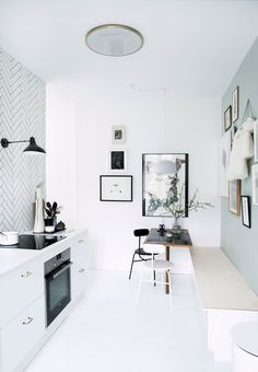 Kitchen with black white and blue. White tiles and black wall light, bench and small (s)eating area