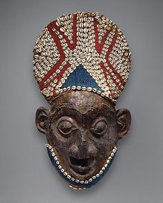 Helmet Mask    Date:      before 1880  Geography:      Cameroon, Grassfields region  Culture:      Bamum kingdom  Medium:      Wood, copper, glass beads, raffia, cowrie shells
