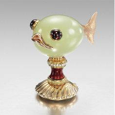 Fabergé jewelled three-colour gold, enamel and bowenite seal, workmaster: Henrik Wigström, St. Petersburg, 1899-1908; the bowenite handle charmingly formed as a small fish with a delicately incised gold tail, a wide gold mouth, cabochon garnet eyes, set on a tapering column of translucent strawberry red guilloché enamel mounted with seed pearls, the base formed as a sea shell, the matrix uncut,