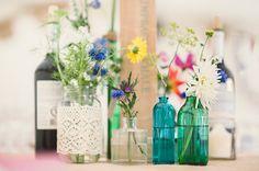 Vintage flessen als vazen gevuld met prachtige, kleurrijke bloemen.