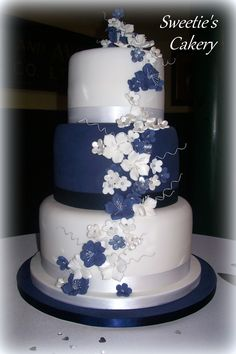 http://facebook.com/SweetiesCakery  Navy blue, white and silver wedding cake with flowers.