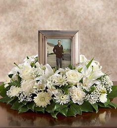 larger portrait surrounded by white flower arrangement, prominently displayed