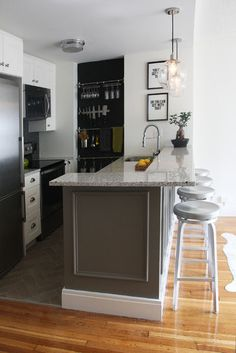 Good job with the renovation. I especially like: herringbone pattern tile work on the floor, trim added to the outer island walls, chalkboard paint along the back wall and use of back wall for wall-mounted storage. Contemporary kitchen by Stephanie Sabbe.