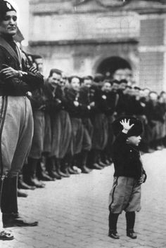 War Child : A uniformed child joins forty thousand teenage Fascists at Rome's Place du Peuple, 1932