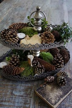 Make your own vintage style tiered holder using thrift store plates with a lip or cake pans and candlesticks. Spray paint them brown or dark grey, then follow with a coat of creamy white, sand to distress slightly and glue together. Add votives and greens!