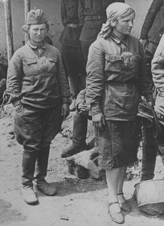 "Two Soviet female POWs at an assembly point on the Eastern Front. The woman in the foreground is wearing dress shoes, the most unlikely footwear for what lies ahead -- long marches. Soviet female POWs were treated as harshly as their male counterparts by the German army engaged in a ""war of annihilation."""