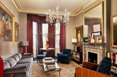 This Village living room has ornate carpets, blue velvet furniture, gilded picture frames, marble fireplace, red curtains and a chandelier.