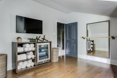A blue door opens to a home gym featuring a flat panel television mounted above wooden towel shelves fitted with a glass front mini beverage fridge, while a ballet barre is fixed in front of a full length mirror. Home Gym Basement, Home Gym Garage, Diy Home Gym, Home Gym Decor, Best Home Gym, Basement Workout Room, Home Yoga Room, Workout Room Home, Gym Room At Home