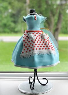 Inspired by a cake previously posted by Shayesmomma....brides shower was a 1950s housewife theme! Chocolate cake with whipped chocolate ganache. The bodice was made of RKT mixed with modeling chocolate. The little pockets have an oven mitt plus a metal spatula. My sister made matching cherry/blueberry pie cupcakes to go with the occassion! Thanks for looking!