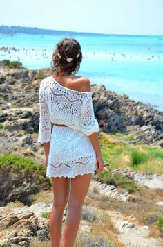 vestido ibicenco, mujer de espaldas en la playa, vestido de encaje blanco corto, un hombro descubierto, pelo recogido con corona de flores