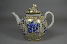 Teapot and cover, porcelain, the domed cover surmounted by a flower knop; painted with blue flowers oove a gilt design. There is a  monogram below the spout.