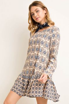 Printed long sleeve drop waist dress featuring deep scooped back with band detail with side pockets. Content + Care: 98% Polyester 2% Spandex Hand Wash