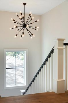 An oil rubbed bronze sputnik chandelier illuminates a white staircase accented w. An oil rubbed bronze sputnik chandelier illuminates a white staircase accented with a black handrai Staircase Lighting Ideas, Stairway Lighting, Entryway Lighting, Wall Lighting, Hallway Chandelier, Sputnik Chandelier, Simple Chandelier, Chandelier Ideas, Black Chandelier