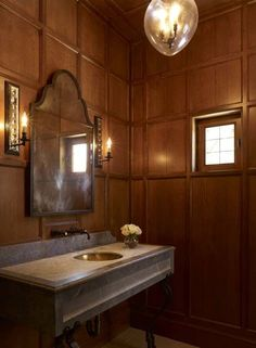 A carved limestone vanity with inlaid marble top and hand forged iron legs is the centerpiece in the paneled powder room in this Texas Hill Country home with Arts & Crafts style architecture designed by Michael G. Imber.