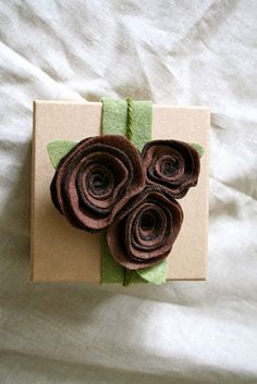 i've been wrapping presents with brown paper for years... love the simplicity and flexibility of decorating with lots of different kinds of ribbon and stickers.... love this idea with the felt flowers.... which are super easy.  this looks so elegant