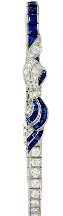 Art Deco Diamond Sapphire Bracelet. An Art Deco diamond and sapphire French cut line bracelet, centering on a bow, in platinum.