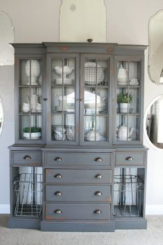 A dark grey (gray tabby) painted hutch with white ironstone, wire baskets and grain sack stripe painted interior. Corner China Cabinets, Painted China Cabinets, Painted Hutch, Refinished China Cabinet, Farmhouse China Cabinet, Hutch Cabinet, China Cabinet Display, Modern China Cabinet, Hutch Display