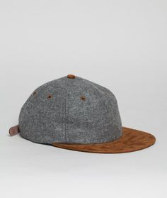 The Wool Flat Cap has been re-imagined in a basic light. Preserving the tactilely pleasing suede brim and durable wool crown, a 6-panel construction and contrasting eyelets are also central to the look.