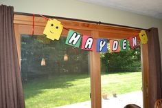 "Our version of the Lego banner.  Used the Lego font I had downloaded to create the letters. Increased the size and then cut them out.  Used simple construction paper bought at Sam's to make the ""blocks"" and hole punched the circles from same paper.  Used a corner punch to round the edges to make the heads.  Red ribbon through hole punches to string it all together!"