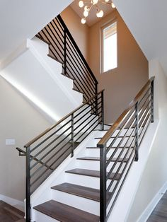 A simple and stylish way to make the staircase look simple yet chic and eye-catching is to use contrasts. In this case, for example, the wooden stairs sit on a crisp white background and the metal guardrail with wooden handrail frame them beautifully. Indoor Railing, Modern Stair Railing, Wrought Iron Stair Railing, Stair Railing Design, Metal Stairs, Staircase Railings, Banisters, Railing Ideas, Stairways