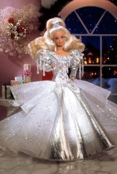 """Special Edition   Release Date: 1/1/1992    Barbie® is ready for the holiday season, dressed in a luxurious, silver lamé gown. The many layers of her tulle skirt are accented with holographic glitter, and shimmering beads dangle from the bodice. Silvery earrings and a silvery """"jewel""""-accented hairband create the finishing touches to this festive ensemble."""
